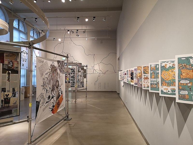 Blick in die Ausstellung CommixConnection im MEK. Am Ende des Raums ein Fadenbild, dass die verschiedenen Orte zeigt mit denen sich die Ausstellung beschäftigt. Rechts an der Wand ein Comic über die Azstellung, links weitere Comics.