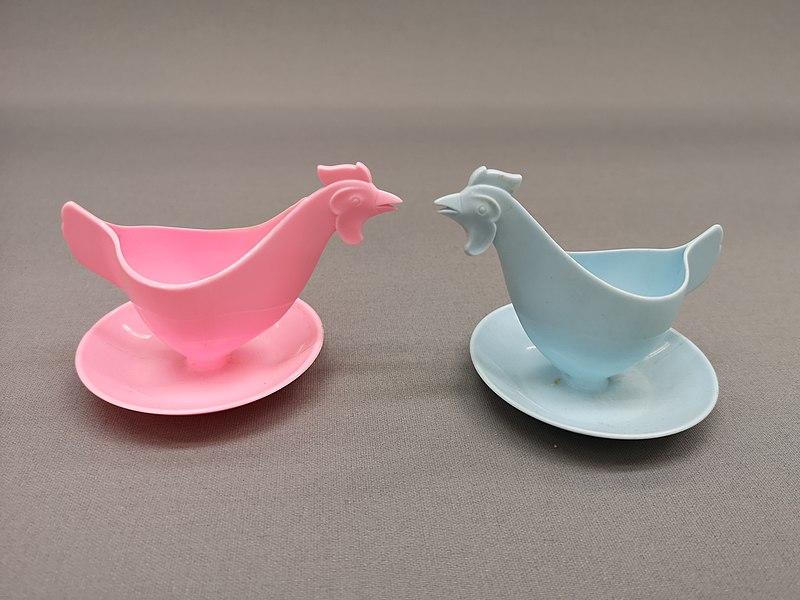 DDR-Eierbecher aus der Sammlung des Museums Europäischer Kulturen. Aus Kunststoff, in der Form von Hühnern. Einer in rosa, einerin hellblau.